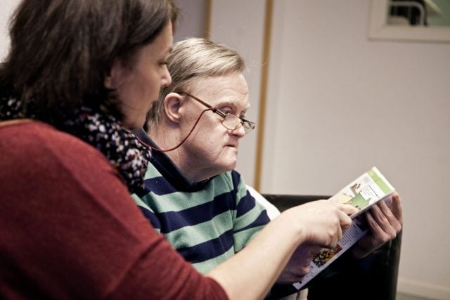 Mature woman assisting senior mentally challenged man in reading book on sofa