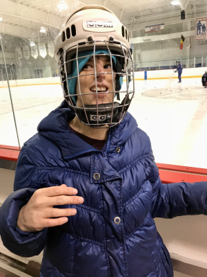 Amy wearing an ice hockey helmet standing near the ice